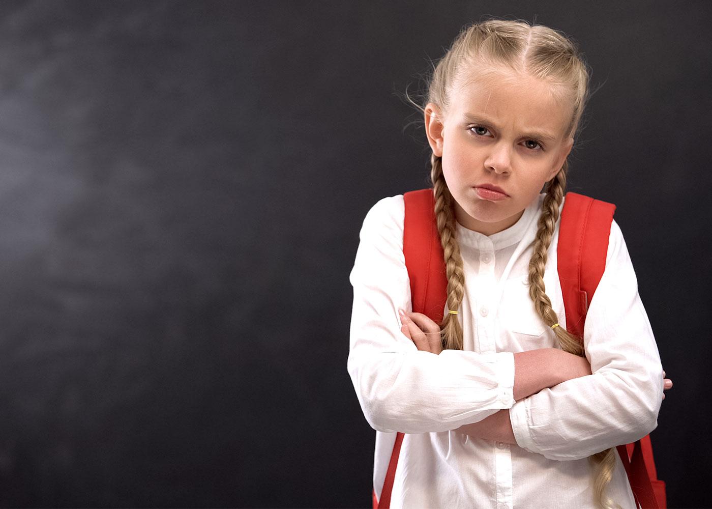 Annoyed schoolgirl with crossed hands