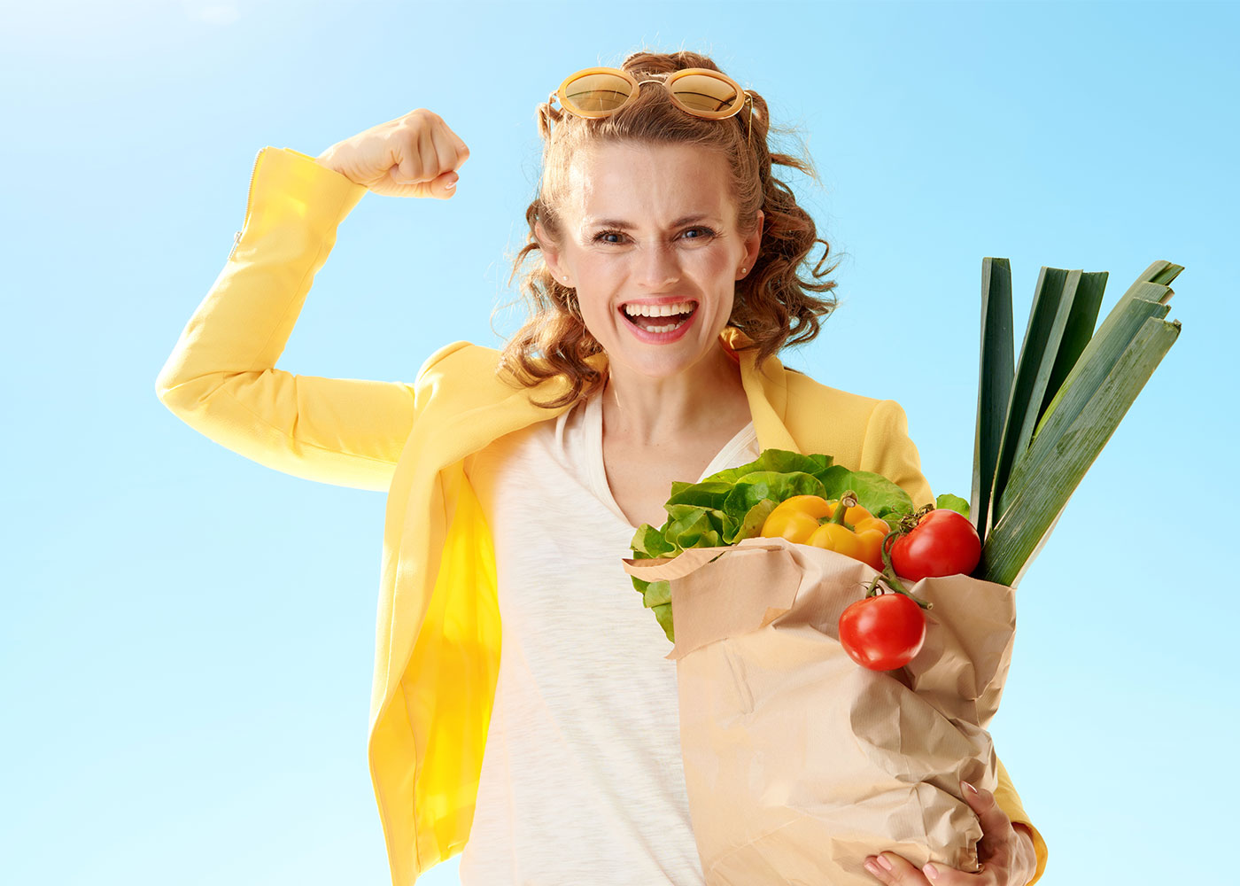 Smiling woman with paper bag with groceries showing biceps