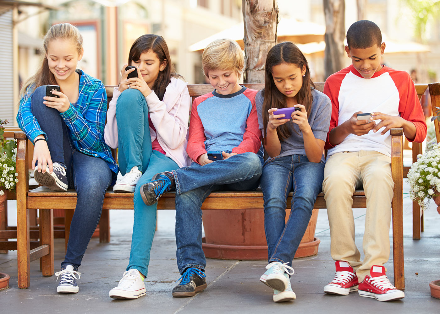 Children Sitting In Mall Using Mobile Phones